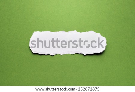 A piece of torn paper on a green background. Space for text. - stock photo