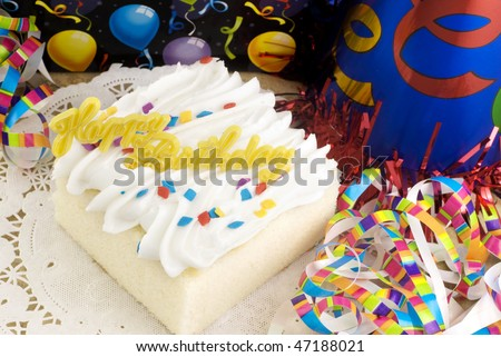 A piece of white cake with a Happy Birthday message, colorful party decorations, horizontal with copy space - stock photo
