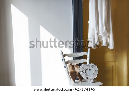 A piece of white dress near door. Shoes and white heart lying on chair. No people, copyspace, indoor, interior, closeup - stock photo