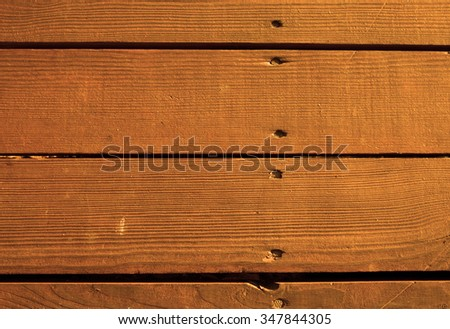 A piece of wooden wall of the old wooden house, boards with visible scratches and pegs pounded nails, background and texture, brown. Horizontal. - stock photo