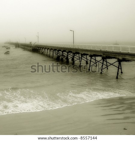 a pier disappearing into the fog in black and white