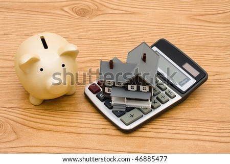 A piggy bank and a calculator sitting on a wooden background, mortgage calculator - stock photo