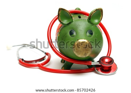 A piggy bank and stethoscope are isolated on white and give representation to an emergency fund. - stock photo