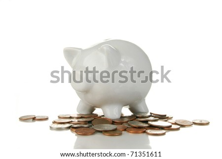 A piggy bank on a white background with coins under it - stock photo