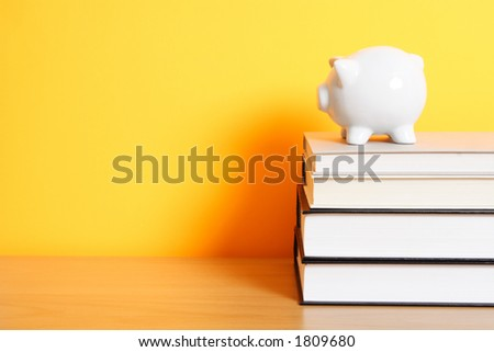 A piggy bank on top of a stack of books, good for saving for college theme - stock photo
