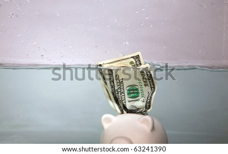 a piggy bank sinks in dark murkey water, representing the idea of drowning in debt, or keeping your head above water and other financial concepts - stock photo