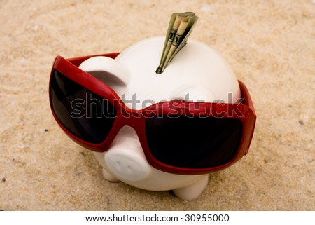 A piggy bank wearing sunglasses on a sand background, vacation savings - stock photo