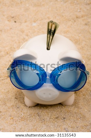 A piggy bank wearing swimming goggles on a sand background, vacation savings - stock photo