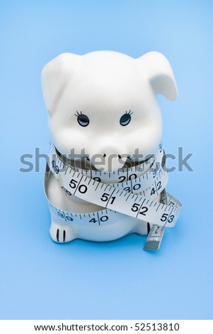 A piggy bank with a measuring tape on a blue background, measuring your savings - stock photo
