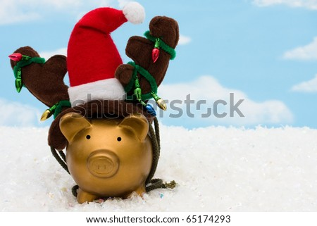 A piggy bank with a santa hat, reindeer antlers and christmas lights on a sky background, christmas savings - stock photo