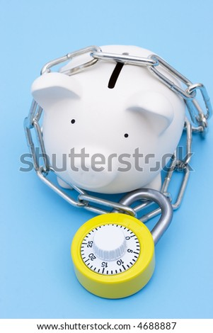 A piggy bank with chains and a bright yellow combination lock - stock photo