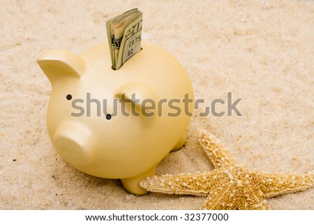 A piggy bank with starfish on a sand background, vacation savings - stock photo