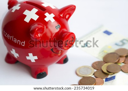 A piggy bank with Switzerland flag near banknotes on the white background