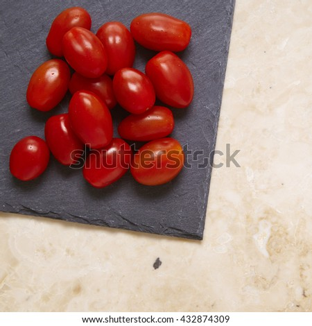 A pile of baby plum cherry tomatoes on a slate chopping board and marble counter top background - stock photo