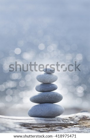 a pile of balanced stones  against a bokeh water background