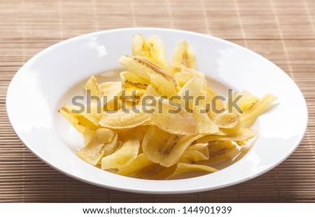 a pile of banana chips on the plate - stock photo