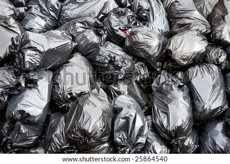 A pile of black garbage bags with tons of trash - stock photo