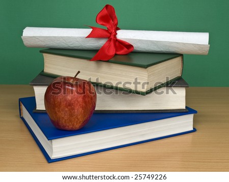 A pile of books, an apple and a diploma. - stock photo