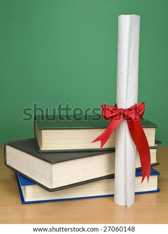 A pile of books and a diploma. Blank chalkboard on the background. - stock photo