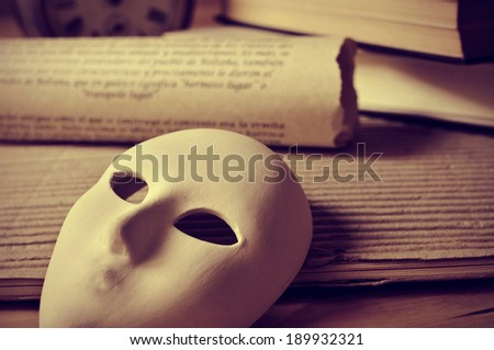 a pile of books and a mask, depicting the concept of playwriting and performing arts - stock photo