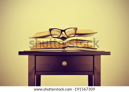 a pile of books and a pair of eyeglasses on a desk, symbolizing the concept of reading habit or studying, with a retro effect - stock photo