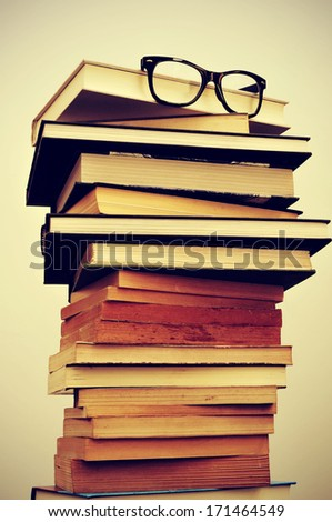 a pile of books and eyeglasses symbolizing the concept of reading habit or studying - stock photo