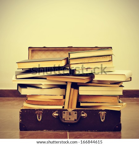a pile of books in an old suitcase with a retro effect - stock photo