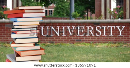 a pile of books in front of university - stock photo