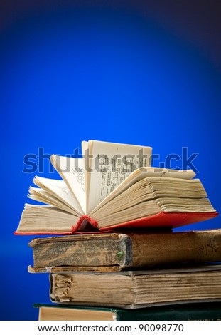 A pile of books on a blue background - stock photo