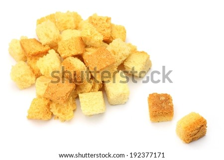 A pile of bread cubes sits on a white surface. - stock photo