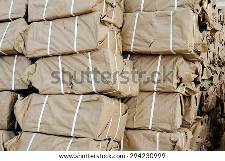 A pile of brown parcel wrapped in brown paper books. - stock photo