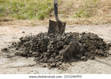A pile of cement wiht a shovel in it - stock photo