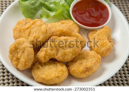 A pile of chicken nuggets on white plate with sauce - stock photo