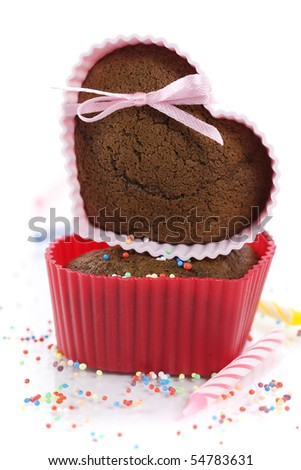 A pile of chocolate heart shape muffins in silicone molds with strawberry and sprinkles - stock photo