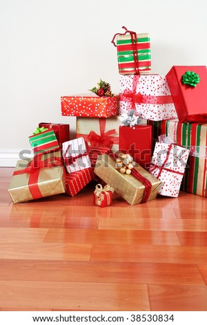 A pile of Christmas gifts in colorful wrapping with ribbons against the wall on a beautiful hardwood floor with copyspace. - stock photo