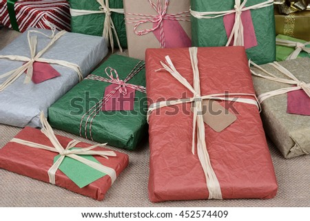 A pile of christmas presents on a burlap surface. The packages are wrapped in colorful tissue paper and plain brown paper. - stock photo