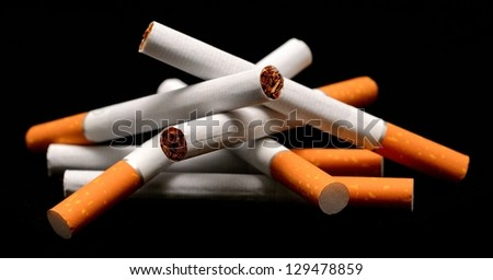 A pile of cigarettes on a black background. - stock photo