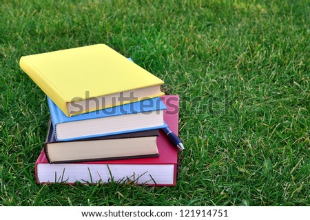 a pile of colorful books on grass in campus - stock photo