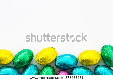 A pile of colorful  Easter eggs at the bottom of the frame on an isolated white background.