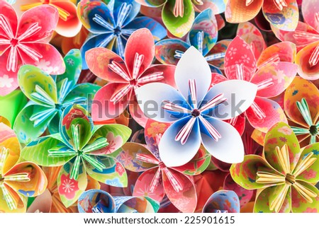 A pile of colorful Japanese Kusudama flower pieces. Shallow depth of field. Focus on the blue/pink flower on top of the pile. - stock photo