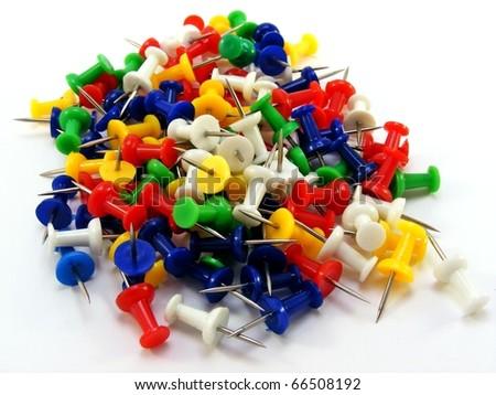 A pile of coloured thumbtacks lying on a white background - stock photo