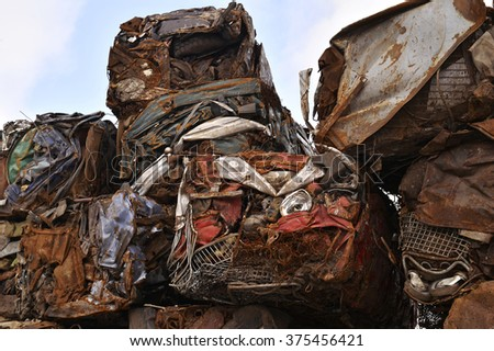 A pile of compressed cars in blocks for processing.