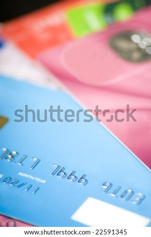 A pile of credit cards with all personal information and logos altered or removed.