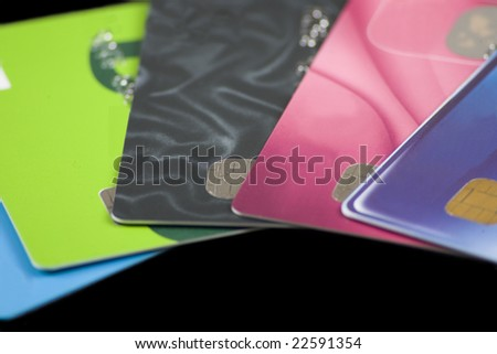 A pile of credit cards with all personal information and logos altered or removed. - stock photo
