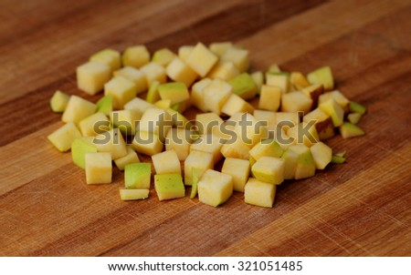 A pile of diced golden delicious on a cutting board. - stock photo