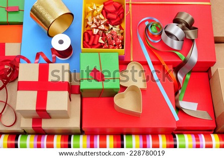 a pile of different boxes, wrapping paper, ribbon and ribbon bows of different colors to prepare gifts - stock photo