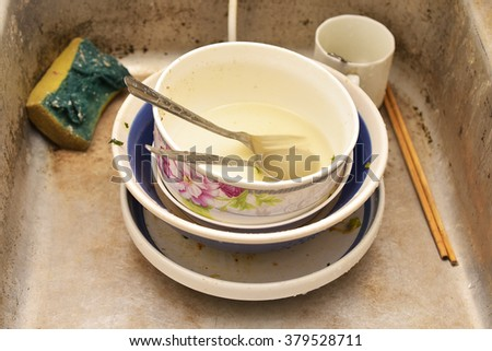 A pile of dirty dishes in a kitchen sink - stock photo