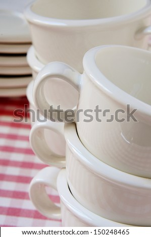 a pile of empty porcelain coffee cups and plates on a checkered tablecloth - stock photo