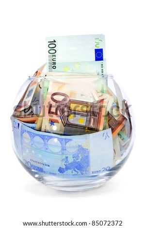 a pile of euro bills into a glass money box