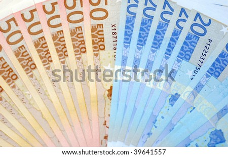 A pile of euro dollars lying on a white surface. - stock photo